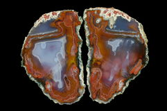 Agate. A cross section of the agate stone. At the top the pseudomorphosis divide agate, slanting thermal cracks are at the bottom. Multicolored silica rings Royalty Free Stock Photography