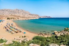 Agathi beach with holiday makers enjoying their time Rhodes, Greece royalty free stock photo