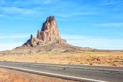 Agathla-Spitze mit der Straße zum Monument-Tal im Vordergrund, Arizona, Vereinigte Staaten stockfotos