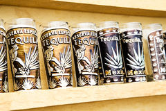 Agave tequila production. Several tequila souvenir glass in wood cabinet Stock Photos