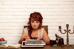 Age barrier. Journalist work in vintage office. Old woman work in writer office. Senior woman type on retro typewriter. Senior writer at desk. Female reporter stock photo