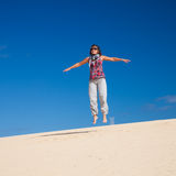 Age doesn't matter. Middle age woman jumps in the dunes Royalty Free Stock Photography