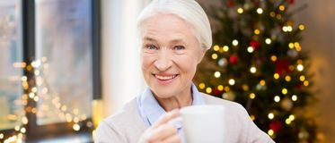 Happy senior woman with cup of coffee. Age, holidays and people concept - happy smiling senior woman with cup of coffee at home over christmas tree lights royalty free stock photography