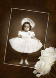 The Age of Innocence. Old vintage picture featuring a little girl posing with white lace dress. Grunge style background and white roses