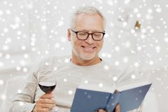 Happy senior man drinking wine and reading book. Age, leisure and people concept - happy smiling senior man with wine glass reading book at home over snow Royalty Free Stock Photo