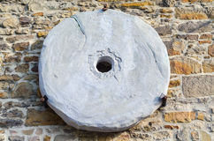 Age millstone. Traditional old millstone hung on a dry stone wall Royalty Free Stock Image