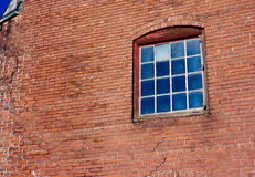 Age Old Brick Building Window Time Nonconformist. A mullioned window with one mismatched pane, in an old brick building with cracks in its walls Royalty Free Stock Images