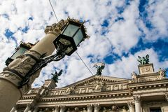 Age-old Iron Street Light on Large Post by Opera House. Age-old iron lace street light on large post against Lvov Opera House and blue sky white clouds Stock Image