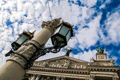Age-old iron street light on large post by opera house. Age-old iron lace street light on large post against Lviv Opera House and blue sky white clouds Royalty Free Stock Photos