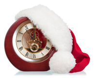 Age-old mechanical clock. And Christmas hat on a white background Stock Photos
