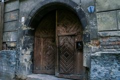 Age-old Wooden Door in House with Peeled off Walls. Age-old wooden door in old city house with peeled off walls in old european city Royalty Free Stock Photography