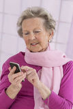Age and people concept - close up of happy senior woman with smartphone at home Stock Photo