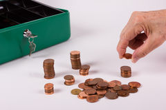 Age poverty among seniors. A Senior sorts his little money at the end of the month in a green cash box stock photography