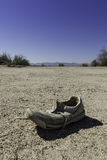 Age shoe. Shoe weathered on the bode of a desert landscape Stock Images