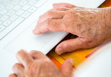 Age spotted hands on the laptop Royalty Free Stock Photography