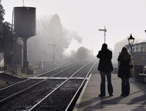 The Age of Steam. Old Steam Train emerging from the Fog and arriving a a station with a couple waiting on the platform Royalty Free Stock Photography
