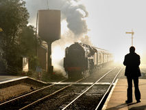 The Age of Steam. An old steam Locomotive emerging through the mist and arriving at a Station in Rural England Stock Photo