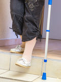 Age woman with a crutch down the stairs Stock Photo