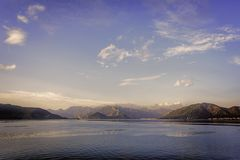 Agean sea shore vista under scattered white clouds on blue skies, golden hour Stock Images