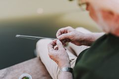 Aged angler putting the bait on the hook. Close up of an elderly man enjoying fishing while putting the bait on the hook stock photo