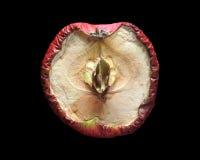 Aged apple. A rotten apple cut in half, dramatic lightning Stock Photos