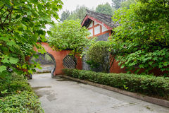 Aged arched gate and building in trees and shrubs Royalty Free Stock Image