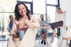 Aged asian businesswoman smiling and drinking coffee while sitting at office Stock Images