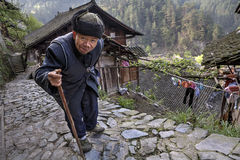 Aged Asian walks along stone road, laying on his stick. Royalty Free Stock Photography