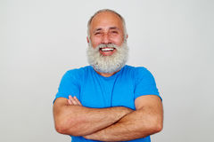 Aged bearded fit man with crossed hands and broad smile against Royalty Free Stock Photography