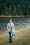 Aged beautiful woman in blue jeans and striped T-shirt standing on the bank of the mountain lake surrounded by forest. Travel concept stock image