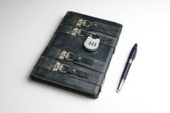 Aged black leather journal locked with the padlock. Black pen lay down on the book side royalty free stock image
