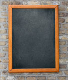 Aged blackboard hanging on brick wall Royalty Free Stock Photo