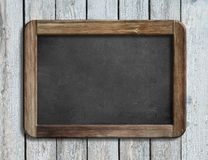 Aged blackboard hanging on white wooden wall 3d illustration Stock Photo