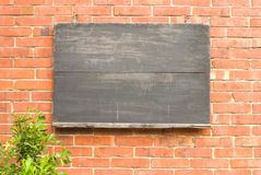 Aged blackboard on red brick wall. Stock Photos