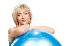 Aged blond woman with fitness ball. Stock Photos