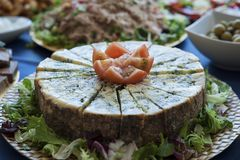 Aged blue cheese wheel, a popular fermented dairy, cut in small even triangles with tomato garnish. Horizontal food shot of blue cheese with a decorative tomato Royalty Free Stock Image