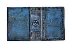 Aged blue leather book cover with the embossed Pentagram, ancient pagan symbol - lay down to the table opened. And isolated stock photos