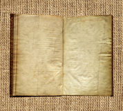 Aged book on burlap background Stock Images