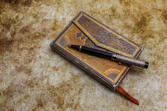 Aged book with ornamented covers and pen Stock Image