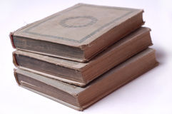 Aged books. Three old books stacked. Books are isolated on white background royalty free stock photo
