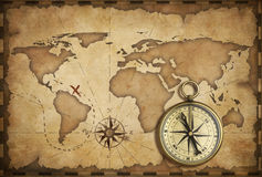Aged brass antique nautical compass and old map. With track on it stock photo