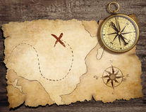 Aged brass antique nautical compass on table. With old treasure map stock photo