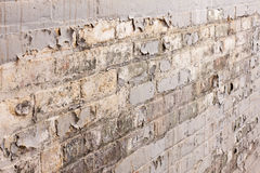 Aged brick wall in old building with peeling paint - background Stock Photo