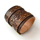 Aged brown leather bracelet filled with embossed skulls - top view stock photo