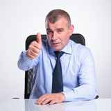Aged business man at desk shows thumb up Stock Image