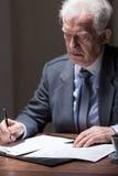 Aged businessman doing paperwork Stock Photo