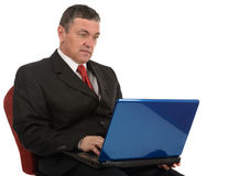 Aged businessman sitting at desk with a laptop isolated on white Royalty Free Stock Images