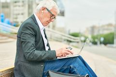 Aged businessman using laptop and listening to music stock images