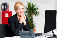 Aged businesswoman sitting with hands on chin Stock Image