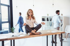 Aged businesswoman sitting on table and meditating in lotus position while colleagues working behind. Middle aged businesswoman sitting on table and meditating Stock Photo
